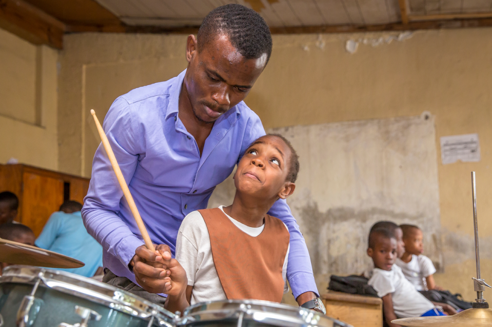 A Teacher and a kid playing drums